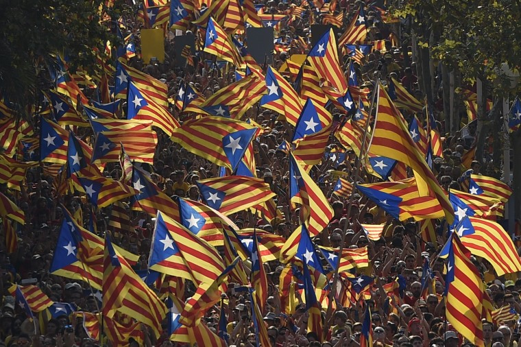 """Catalan hold Catalan independentist flags (Estelada) during celebrations of Catalonia National Day (Diada) in Barcelona on September 11, 2014. Red and yellow flags filled the streets of Barcelona today as Catalan nationalists fired up by Scotland's independence referendum rallied to demand a vote on breaking away from Spain. Demonstrators planned to mass in the late afternoon along two central Barcelona avenues in the shape of a giant letter """"V"""" for vote. LUIS GENE/AFP/Getty Images"""