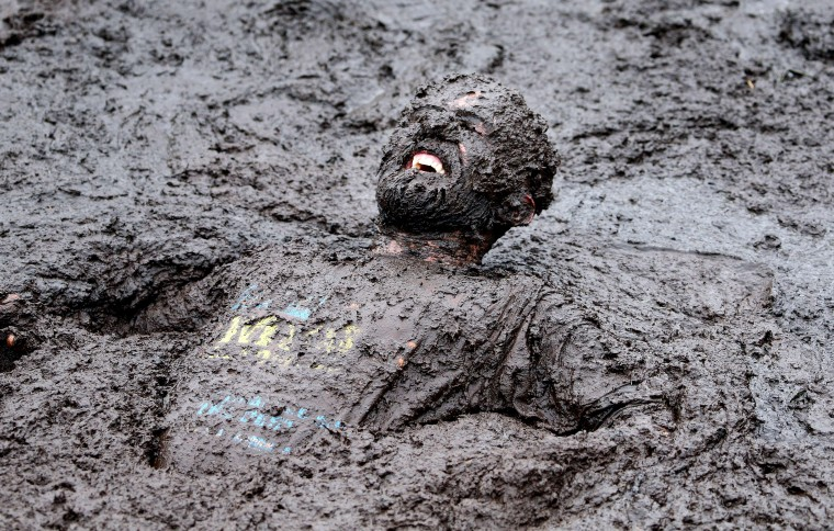 A competitor competes in the Mud Madness race, at Foymore Lodge in Portadown, County Armagh on September 14, 2014. Some 800 Competitors ran, crawled and belly-flop their way across four and half miles of bogs and ponds, under cargo nets and through water sprays and muddy trenches in aid of Charity. PAUL FAITH/AFP/Getty Images
