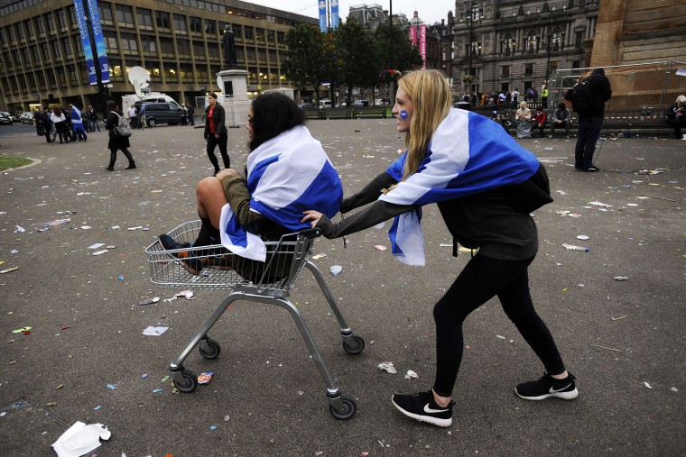 Pro-independence supporters push each other in a shopping trolley in Glasgow, Scotland, on September 19, 2014, following a defeat in the referendum on Scottish independence. Scotland rejected independence on Friday in a referendum that left the centuries-old United Kingdom intact but paved the way for a major transfer of powers away from London. ANDY BUCHANAN/AFP/Getty Images