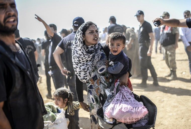 A Syrian Kurdish woman crosses the border between Syria and Turkey at the southeastern town of Suruc in Sanliurfa province on September 23, 2014. The UN refugee agency warned Tuesday that as many as 400,000 people may flee to Turkey from Syria's Kurdish region to escape attacks by the Islamic State group. BULENT KILIC/AFP/Getty Images