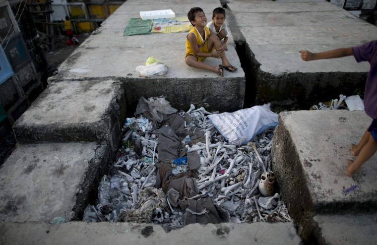 Children living inside the cemetery play near human bones on top of stacked graves at the Navotas Public Cemetery in Manila on October 31, 2014, days ahead of the traditional All Souls' day. Millions across the Philippines will visit cemeteries to pay their respects to their dead, in an annual tradition that combines catholic religious rites with the country's penchant for festivity. NOEL CELIS/AFP/Getty Images