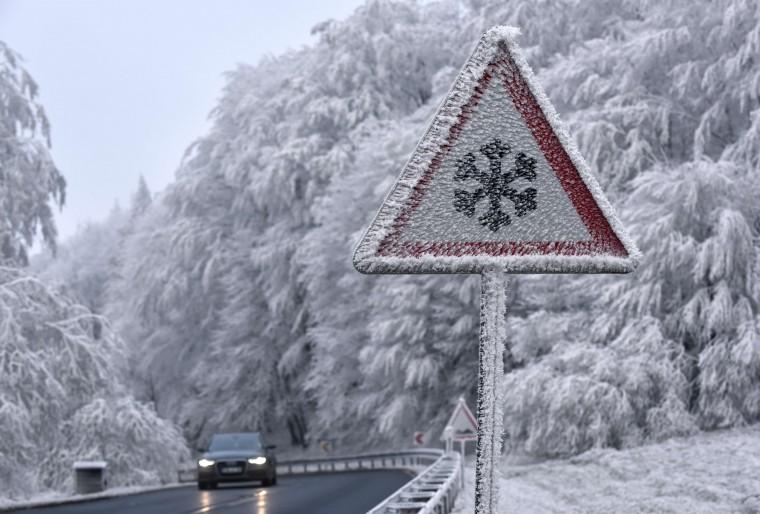A car drives past an ice and snow warning sign near Hessisch Lichtenau, central Germany, on December 2, 2014. (Uwe Zucchi/AFP/Getty Images)
