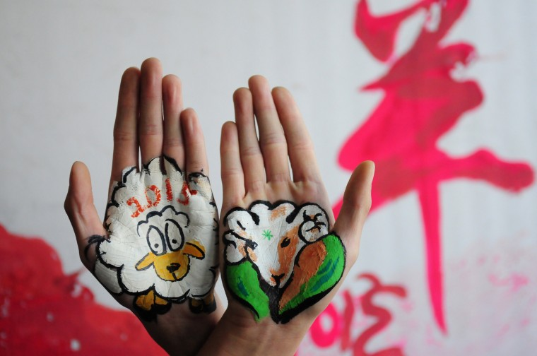 "This photo taken on December 30, 2014 shows college students with paintings of sheep on their hands to welcome the new year, and to mark the coming ""Year of the Sheep"", in Liaocheng, in eastern China's Shandong province. The Year of the Sheep, according to the lunar new year calendar, will start on February 19, 2015. (AFP/Getty Images)"