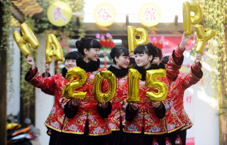 "This photo taken on December 30, 2014 shows guides in a Chinese park posing with balloons that read ""Happy 2015"", to give out new year wishes to tourists at the park in Yangzhou, in eastern China's Jiangsu province. (AFP/Getty Images)"