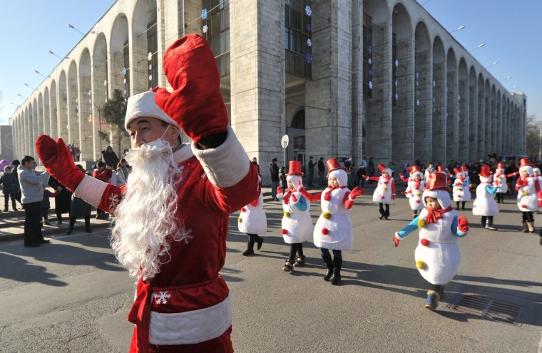 A man dressed as Father Frost, the equivalent of Santa Claus, and children as snowmen take part in a New Year's parade in the Kyrgyz capital Bishkek on December 31, 2014. New Year, which was the biggest informal holiday of the year in the former Soviet Union, is also very popular in the predominantly Muslim Central Asian nation of Kyrgyzstan. (Vyacheslav Oseledko/AFP/Getty Images)