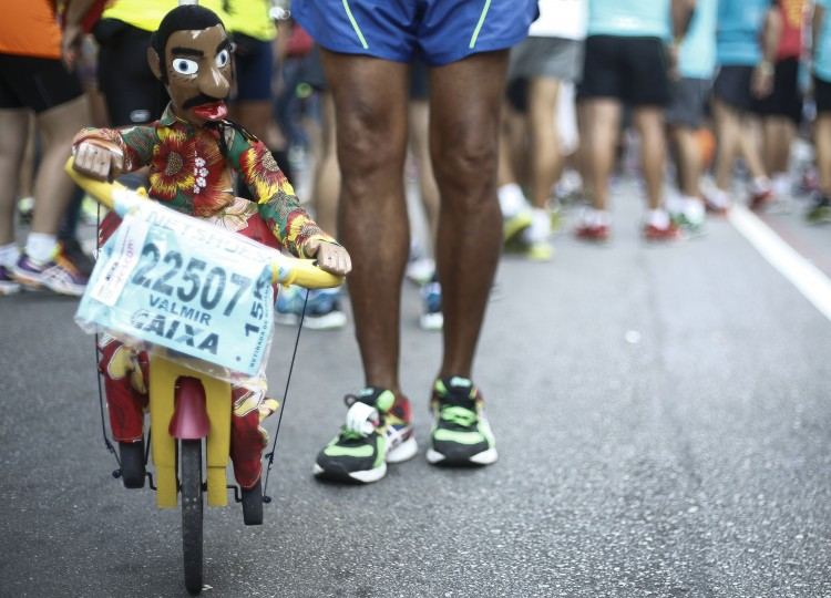 A man carrying a puppet is seen before the 90th Sao Silvestre international 15 km race in Sao Paulo, Brazil on December 31, 2014. Thirty thousand runners participated in the 15 km traditional New Year's Eve event. (Miguel Shincariol/AFP/Getty Images)