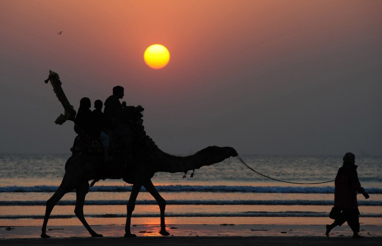 Pakistanis tourists ride on a camel during the last sunset of the year at Clifton beach in Karachi on December 31, 2014. (Asif Hassan/AFP/Getty Images)
