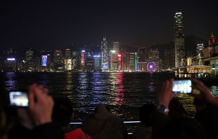 Thousands line Victoria Harbour before the New Year fireworks in Hong Kong on December 31, 2014. Just like previous years, the city's iconic skyline along Victoria Harbour will light up with an eight-minute pyrotechnic display, as tens of thousdands of partygoers will flock to the waterfront to celebrate. (Isaac Lawrence/AFP/Getty Images)