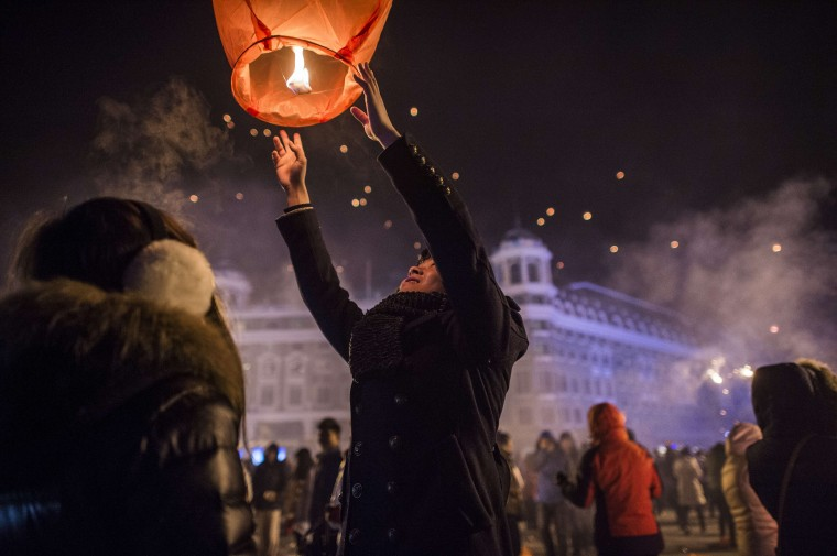 People release sky lanterns to celebrate the New Year in Harbin, on January 1, 2015. Over one million visitors are expected to attend the spectacular Harbin Ice Festival, where buildings of ice are bathed in ethereal lights and international ice sculptors compete for honours. (Fred Dufour/AFP/Getty Images)