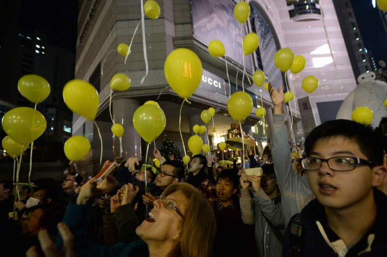 Pro-democracy protesters release over 100 yellow balloons to mark the new year outside a Hong Kong shopping mall on January 1, 2015. After Hong Kong authorities cleared major protest sites that occupied stretches of highways for more than two months, democracy campaigners have found different ways to make their voices heard, with large banners appearing on landmarks and smaller protest gatherings taking place. The yellow colour is a symbol of the city's democracy movement. (Aaron Tam/AFP/Getty Images)