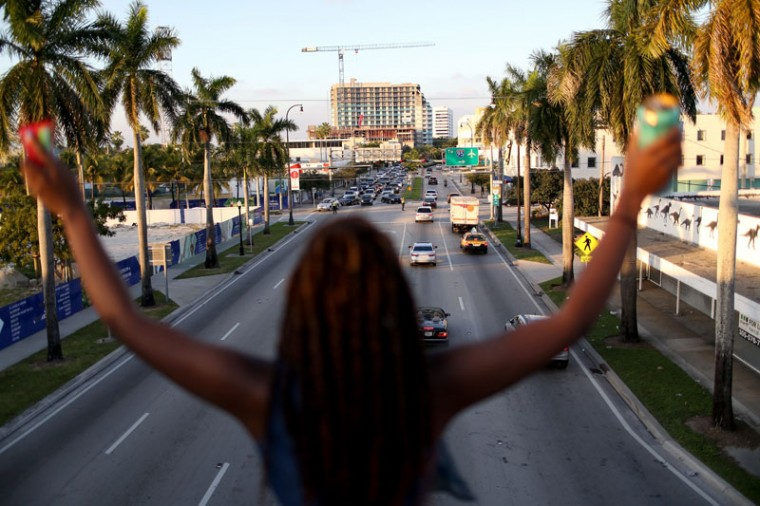 A demonstrator holds her arms up as she joins with others marching along Interstate 195 after police shut the road down on December 7, 2014 in Miami, Florida. The protest was one of many that have take place nationwide after grand juries investigating the deaths of Michael Brown in Ferguson, Missouri and Eric Garner in New York failed to indict the police officers involved in both incidents (Joe Raedle/Getty Images)