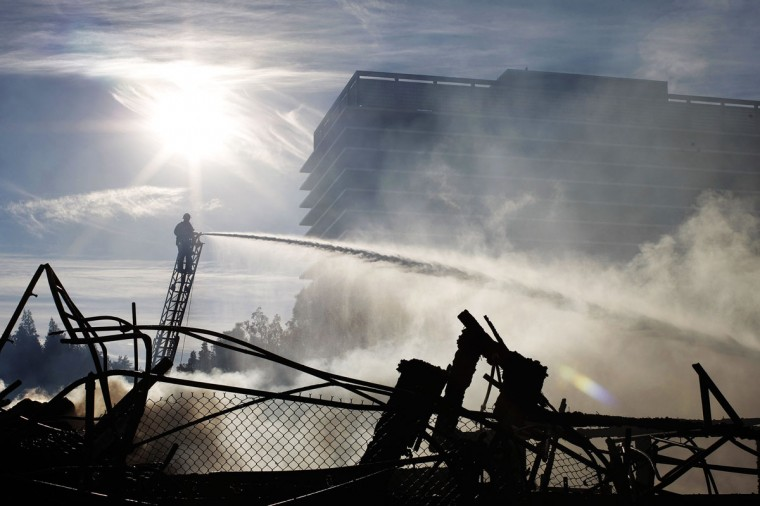 Firefighters hose down the smoldering ruins of a seven-story apartment building under construction alongside the 110 freeway that was destroy in an early morning fire on December 8, 2014 in Los Angeles, California. The fire also damaged nearby high-rise buildings and shut down freeways, causing massive traffic problems for morning commuters. (David McNew/Getty Images)