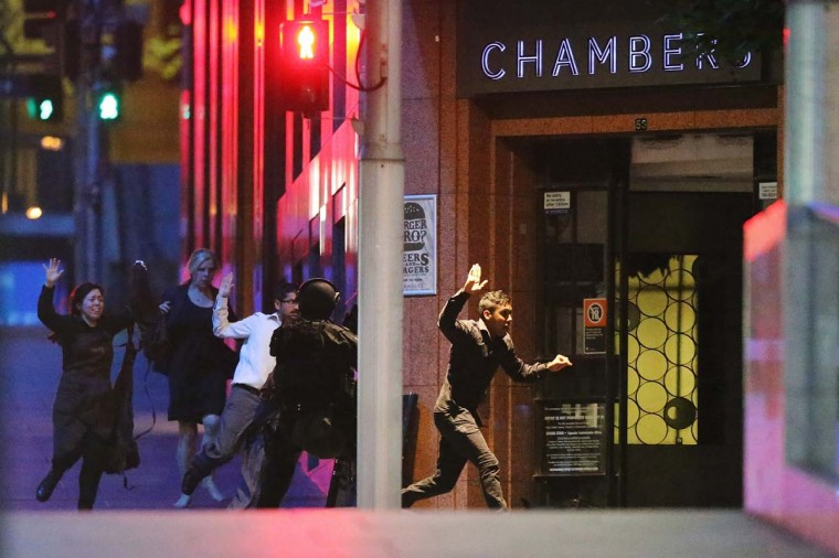 People run with their hands up from the Lindt Cafe, Martin Place during a hostage standoff on December 16, 2014 in Sydney, Australia. Police stormed the Sydney cafe as a gunman has been holding hostages. (Joosep Martinson/Getty Images)