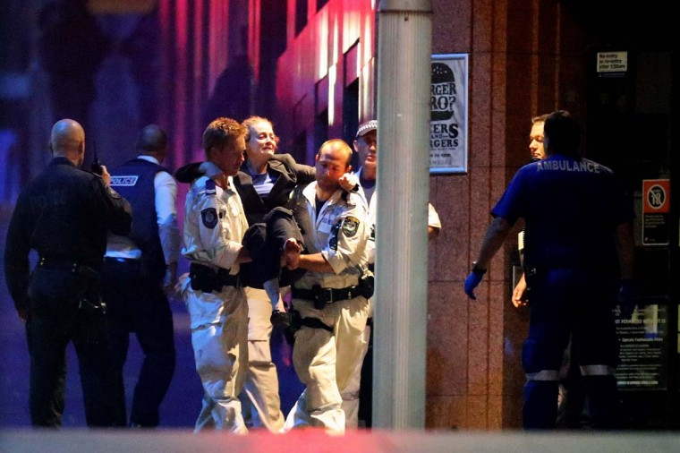 A woman carried out by police from the Lindt Cafe, Martin Place following a hostage standoff on December 16, 2014 in Sydney, Australia. Police stormed the Sydney cafe as a gunman had been holding hostages. (Joosep Martinson/Getty Images)