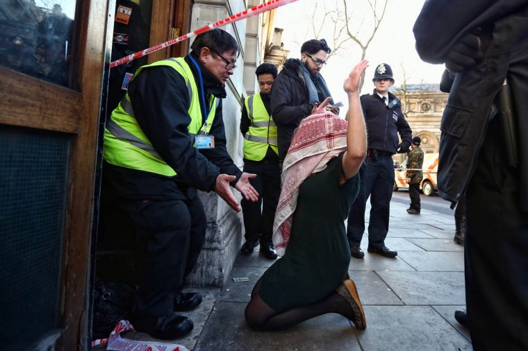 A security guard gestures at a protester outside a building taken over by squatters from a group calling themselves 'Love Activists' on December 24, 2014 in London, England. Previously leased by the Royal Bank of Scotland group, the squatters plan to open the building on Christmas Day and provide a free lunch for homeless people in a protest against the housing crisis. (Carl Court/Getty Images)