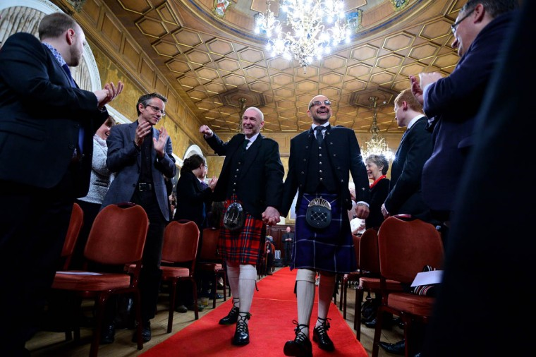Gay couple Joe Schofield (blue kilt) and Malcolm Brown from Tullibody, Clackmannanshire are married in the Trades house shortly after midnight in front of friends and family in one of the first same-sex weddings in Scotland on December 31, 2014 in Glasgow, Scotland. Same-sex couples have been able to enter into 'civil partnerships' since 2005, however following a change in the law in March 2014 gay couples are now eligible to marry in Scotland. Parliament's decision to grant same-sex couples an equal right to marriage has been met with opposition from religious groups. Gay marriage is already legal in England and Wales, however the Northern Ireland administration has no plans to make it law. (Mark Runnacles/Getty Images)