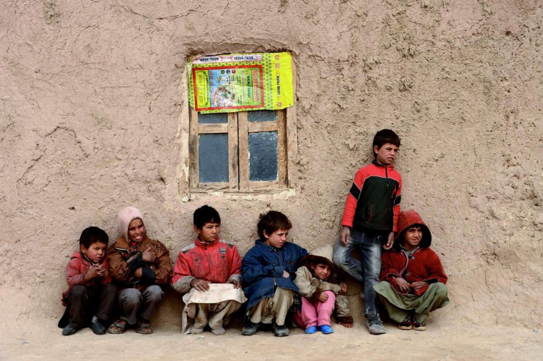 Afghan children sit near their home in Herat on November 30, 2014. As winter sets in across Central Asia, many Afghans struggle to provide adequate food and shelter for their families. (Aref Karimi/AFP/Getty Images)