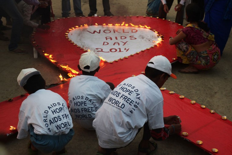 Indian social activists light lamps around a sign during an event to mark World AIDS Day in Kolkata on December 1, 2014. According to the UN AIDS programme, India had the third-largest number of people living with HIV in the world at the end of 2013 and it accounts for more than half of all AIDS-related deaths in the Asia-Pacific region. In 2012, 140,000 people died in India because of AIDS. The Indian government has been providing free antiretroviral drugs for HIV treatment since 2004, but only 50 percent of those eligible for the treatment were getting it in 2012, according to a report by the World Health Organization. (Dibyangshu Sarkar/AFP/Getty Images)