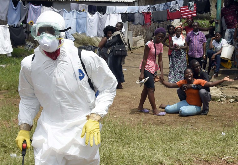 People look on as a woman reacts after her husband is suspected of dying from the Ebola virus, in the Liberian capital Monrovia, on October 4, 2014. (PASCAL GUYOT/AFP/Getty Images)