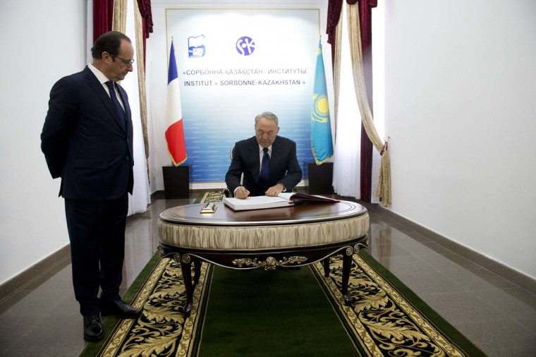 """France's President Francois Hollande (left) looks on as Kazakhstan's President Nursultan Nazarbayev signs the guests' book, during the inauguration of the """"Sorbonne-Kazakhstan """" institute in Almaty, on December 6, 2014 as part of Hollande's two-day visit to Kazakhstan. (ALAIN JOCARD/AFP/Getty Images)"""
