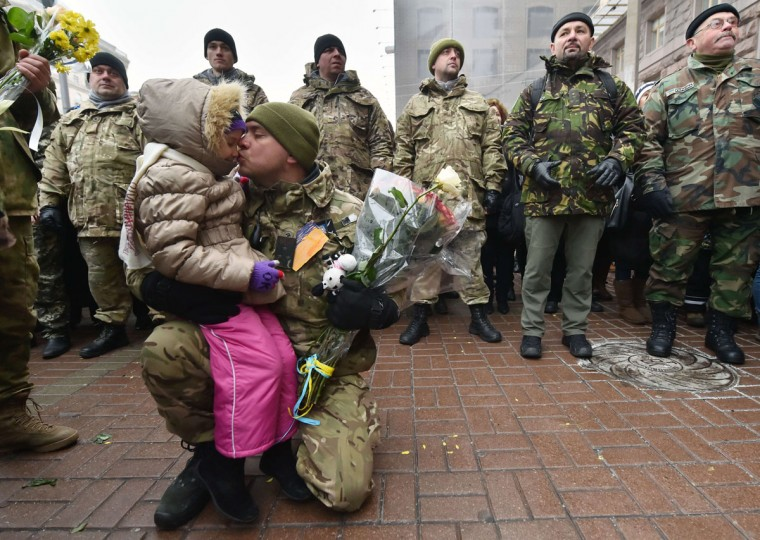 """People greet to servicemen of the Ukrainian volunteer battalion """"Kiev 12"""" who took part in anti-terrorists operation (ATO) in the east of the country and have come back for a two-week rest, during a welcoming ceremony in the center of Kiev on December 6, 2014. Ukraine's foreign minister said Friday that his war-torn country needed a """"real"""" ceasefire, a day after Ukraine and pro-Russian rebels agreed on a fresh truce starting on December 9. (SERGEI SUPINSKY/AFP/Getty Images)"""
