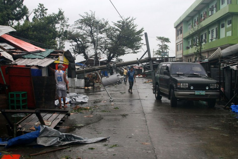 A man walks under a fallen electric post in Tacloban, central Philippines on December 7, 2014. Typhoon Hagupit tore apart homes and sent waves crashing through coastal communities across the eastern Philippines on December 7, creating more misery for millions following a barrage of deadly disasters. (Marlon Tano/AFP/Getty Images)