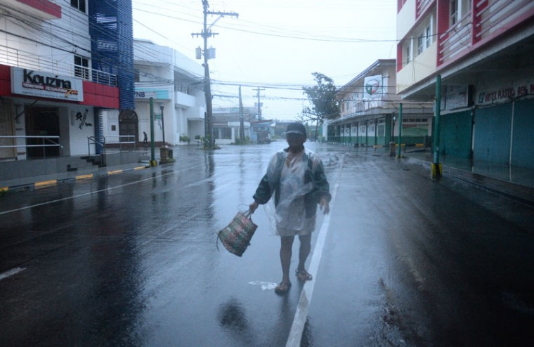 A resident braves strong wind and rain as he heads to the market, hours before Typhoon Hagupit passes near the city of Legazpi on December 7, 2014. Typhoon Hagupit tore apart homes and sent waves crashing through coastal communities across the eastern Philippines, creating more misery for millions following a barrage of deadly disasters. (Ted Aljibe/AFP/Getty Images)