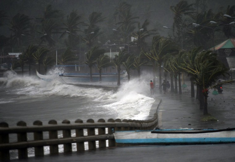 Residents walk past high waves brought about by strong winds as it pound the seawall, hours before Typhoon Hagupit passes near the city of Legazpi on December 7, 2014. Typhoon Hagupit tore apart homes and sent waves crashing through coastal communities across the eastern Philippines, creating more misery for millions following a barrage of deadly disasters. (Ted Aljibe/AFP/Getty Images)