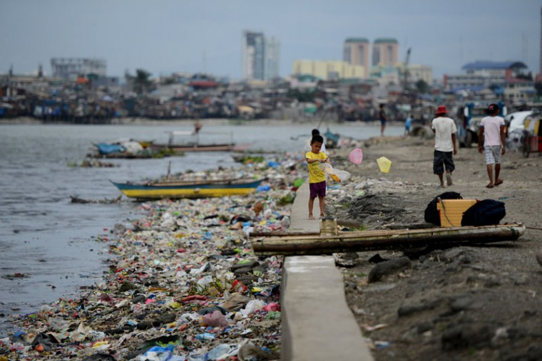A boy plays next to a seawall in a shanty town at the port area in Manila on December 7, 2014 ahead of the arrival of Typhoon Hagupit. Shanties at the bay of Manila will be affected as Typhoon Hagupit will pass near Manila. Typhoon Hagupit tore apart homes and sent waves crashing through coastal communities across the eastern Philippines on December 7, creating more misery for millions following a barrage of deadly disasters. (Noel Celis/AFP/Getty Images)