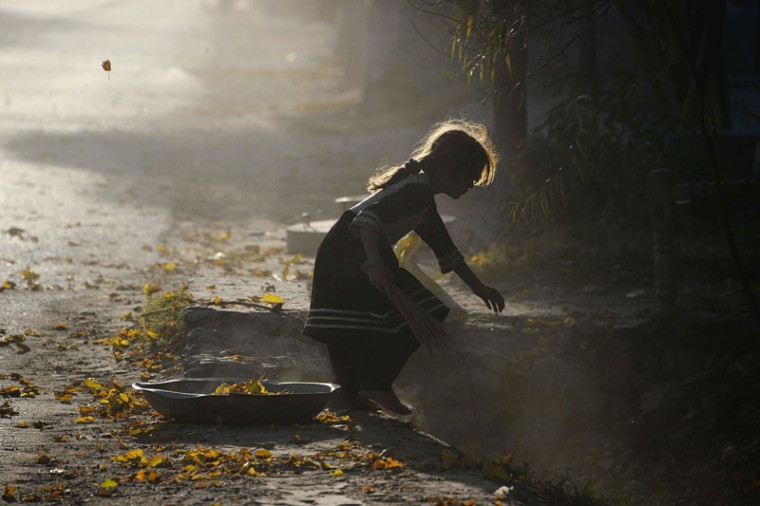 An Afghan girl collects fallen autumn leaves in Jalalabad on December 7, 2014. Poverty and an ongoing insurgency by the ousted Taliban still pose a threat to the stability of the country. (Noorullah Shirzada/AFP/Getty Images)