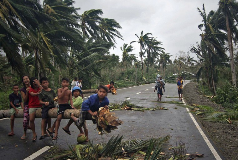 Children play on top of a fallen coconut tree blocking a highway in San Julian town, Eastern Samar province central Philippines on December 8, 2014 in the aftermath of typhoon Hagupit. Millions of people in the Philippine capital hunkered down on December 8 as a major storm churned towards the megacity, after killing at least 21 people and destroying thousands of homes on remote islands. (Vincent Go/AFP/Getty Images)