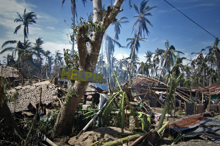 Destroyed houses and trees with a slogan calling for help are seen along a road in the village of Mantang, Taft town Eastern Samar province central Philippines on December 8, 2014, a day after typhoon Hagupit hit the province. Millions of people in the Philippine capital hunkered down December 8 as a major storm churned towards the megacity, after killing at least 21 people and destroying thousands of homes on remote islands. (Vincent Go/AFP/Getty Images)