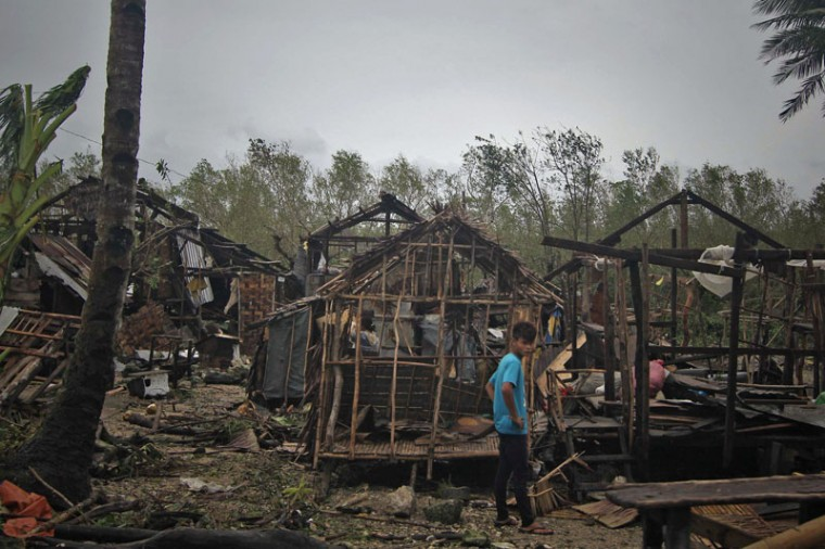 A resident stands in front of houses destroyed at the height of typhoon Hagupit in Borongan City, eastern Samar province central Philippines on December 8, 2014. Millions of people in the Philippine capital hunkered down December 8 as a major storm churned towards the megacity, after killing at least 21 people and destroying thousands of homes on remote islands. (Vincent Go/AFP/Getty Images)