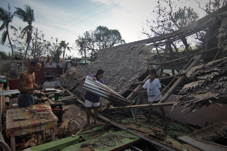 A family try to salvage recyclable roof materials made of nipa leaves from their destroyed house in Dolores town, in Eastern samar province central Philippines on December 8, 2014, a day after typhoon Hagupit hit the province. Millions of people in the Philippine capital hunkered down December 8 as a major storm churned towards the megacity, after killing at least 21 people and destroying thousands of homes on remote islands. (Vincent Go/AFP/Getty Images)