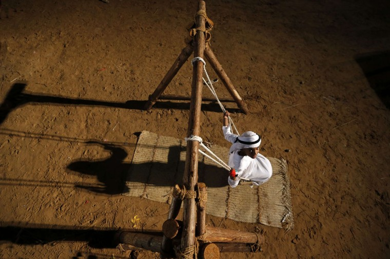 A young Emirati rides on a wooden swing during the 2014 Sheikh Zayed Heritage Festival in Abu Dhabi on December 8, 2014. (Karim Sahib/AFP/Getty Images)