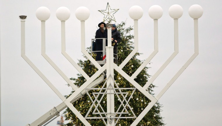 A rabbi works on a eight- branched Hanukkah candelabrum in front of a christmas tree in Berlin, on December 15, 2014. On behalf of the 25th anniversary of the fall of the Berlin wall, Europe's largest candelabrum is placed in front of the Brandenburg's gate on the eve of the start of the eight-day Jewish holiday Festival of Lights. (Jörg Carstensen/AFP/Getty Images)