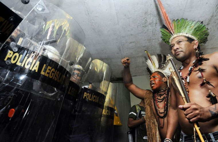 Brazilians natives are blocked from entering the Chamber of Deputies in Brasilia, Brazil on December 16, 2014, during a protest against the new demarcation of indigenous lands bill that is being discussed in Congress --after being passed by the Executive. Agencia Brasil/Antonio Cruz/AFP/Getty Images