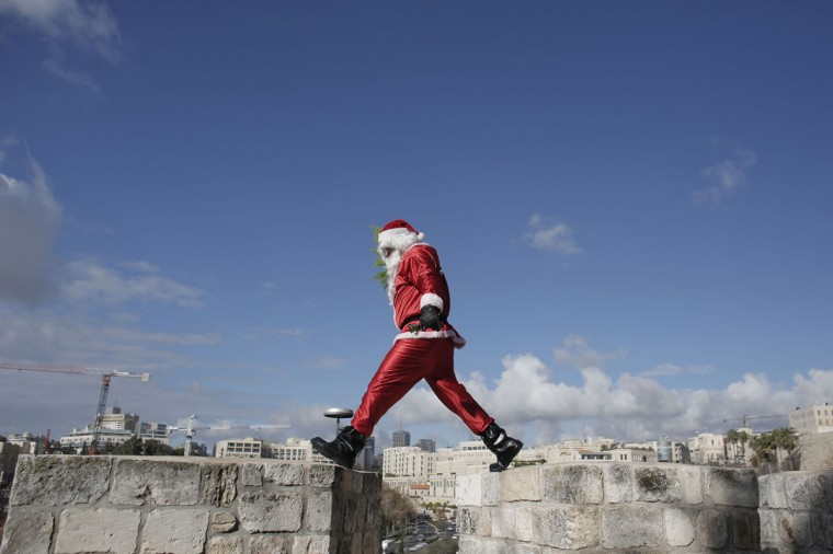 A Palestinian man dressed up as Santa Claus distributes Christmas trees along the wall of Jerusalem's Old City, on December 22, 2014, as Christians around the world prepare to celebrate the holy day. ( Ahmad Gharabli/AFP/Getty Images)