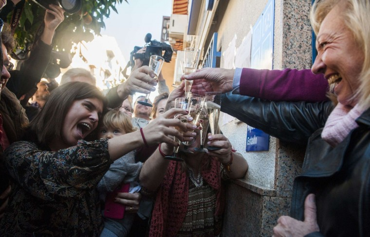 """Lottery Administration shop owners on General Pastor Avenue in Eliana near Valencia celebrate having sold the first prize in Spain's Christmas lottery named """"El Gordo"""" (Fat One) on December 22, 2014. This year's winning number is 13437 representing takings of 4 million euros. (Jose Dordan/AFP/Getty Images)"""