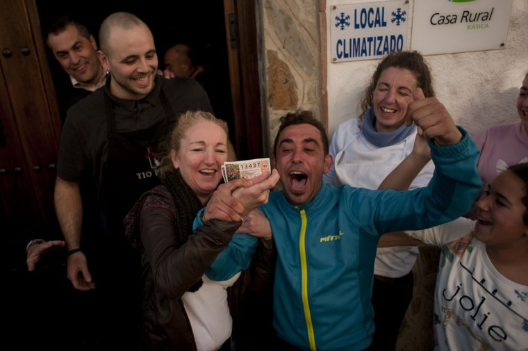 """Spanish Christmas lottery winners pose with their winning ticket in El Bosque, Cadiz province, after having won the first prize in Spain's Christmas lottery named """"El Gordo"""" (Fat One) on December 22, 2014. This year's winning number is 13437 representing takings of 4 million euros. (Jorge Guerrero/AFP/Getty Images)"""