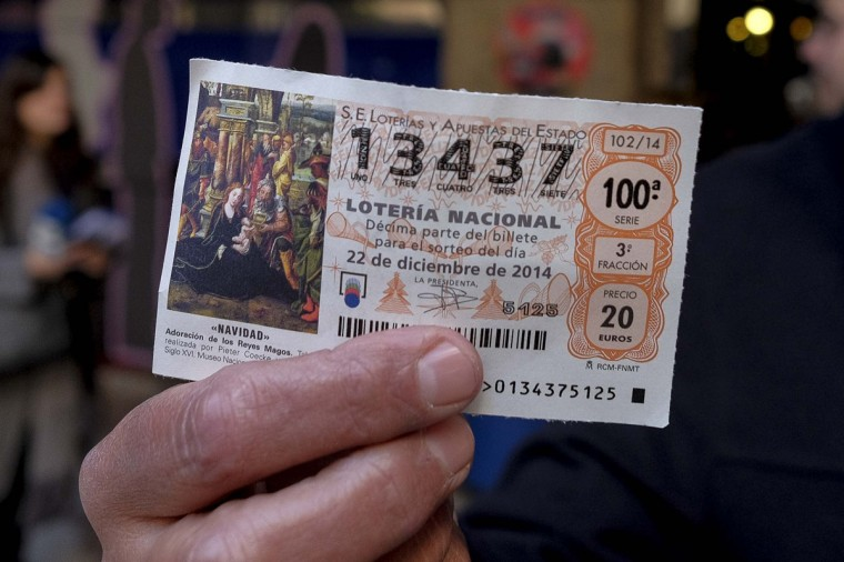"""An employee from Madrid's wax museum in Madrid shows a first prize ticket in Spain's Christmas lottery named """"El Gordo"""" (Fat One) in Madrid on December 22, 2014. This year's winning number is 13437 presenting winnings of 4 million euros. (Pedro Armestre/AFP/Getty Images)"""