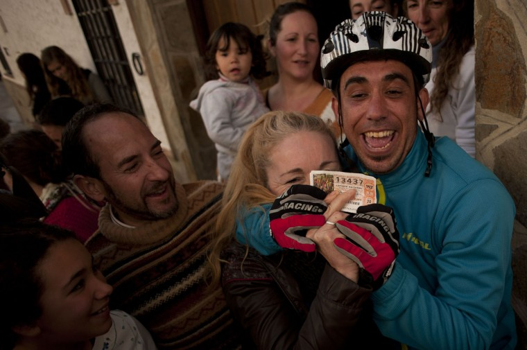 """Spanish Christmas lottery winners celebrate in El Bosque, Cadiz province, after having won the first prize in Spain's Christmas lottery named """"El Gordo"""" (Fat One) on December 22, 2014. This year's winning number is 13437 representing takings of 4 million euros. (Jorge Guerrero/AFP/Getty Images)"""
