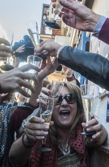 """Lottery Administration shop owners on General Pastor Avenue in Eliana near Valencia celebrate having sold the first prize in Spain's Christmas lottery named """"El Gordo"""" (Fat One) on December 22, 2014. This year's winning number is 13437 representing takings of 4 million euros. (Jose Jordan/AFP/Getty Images)"""