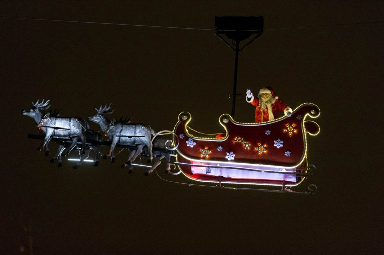 A man wearing a Santa Claus costume waves from his sleigh as he is carried over the Champs Elysees avenue in Paris. (Kenzo Tribouillard/Getty Images)