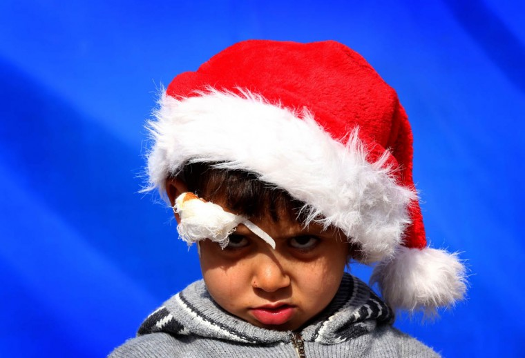 An Iraqi Christian boy, who fled the violence in the northern Iraqi city of Mosul, poses for a photo wearing a Father Christmas hat in the grounds of Mar Elia Chaldean Catholic Church, where many displaced Christians have erected tents, in Arbil, the capital of the Kurdish autonomous region in northern Iraq. For many faithful across the region, the Christmas festivities will be tinged with sadness following a year of bloodshed marked by a surge in the persecution of Christians that has drawn international condemnation. (Safin Hamed/Getty Images)