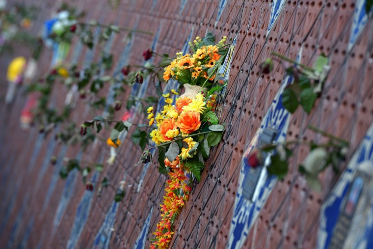 Flowers are displayed on the Ban Nam Khem tsunami memorial park wall on the tenth anniversary of the 2004 tsunami in Phang-nga province on December 26, 2014. Prayer recitals and solemn visits to mass graves marked the start of mourning on December 26 across tsunami-hit nations for the 220,000 people who perished when giant waves decimated coastal areas of the Indian Ocean a decade ago. AFP/Getty/Pornchai Kittiwongsakul