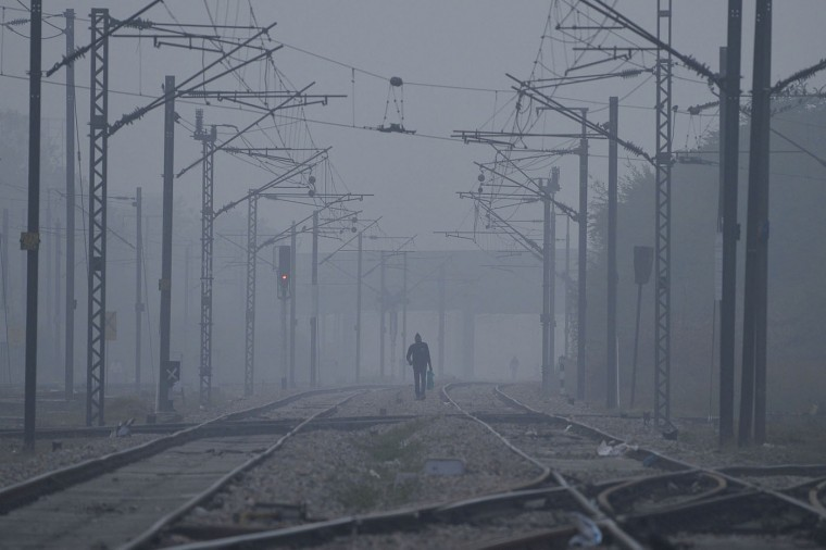 An Indian pedestrian walks along railway tracks during a cold winter morning in New Delhi on December 26, 2014. The city experienced a dense foggy morning with the low visibility affecting road, rail and air traffic. AFP/Getty/Chandan Khanna