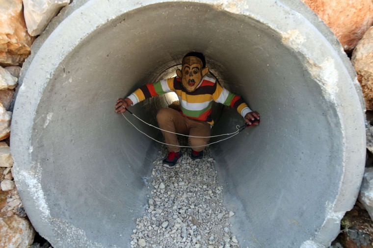 A Palestinian boy, wearing a mask hides in a pipe during clashes with Israeli soldiers in the West Bank village of Bilin, west of Ramallah, following a march organized in solidarity with the people of the village against the construction of settlements and the confiscation of their land on December 26, 2014. AFP/Getty/Abbas Momani