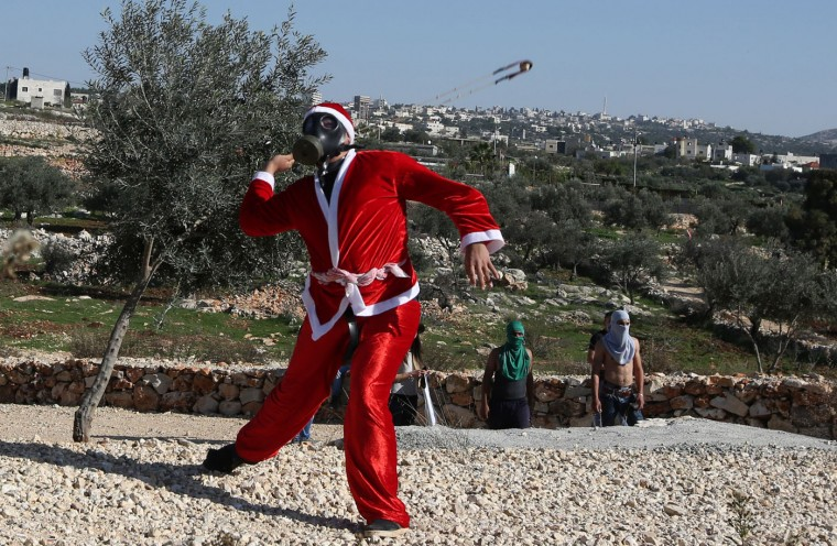 A Palestinian man, wearing a Santa Claus costume and waving the national flag, hurls a rock at Israeli soldiers during clashes in the West Bank village of Bilin, west of Ramallah, following a march organized in solidarity with the people of the village against the construction of settlements and the confiscation of their land on December 26, 2014. AFP/Getty/Abbas Momani