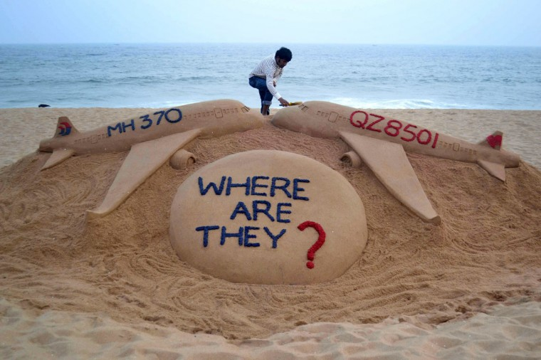 Indian sand artist Sudarsan Pattnaik gives the final touches to his sand sculpture portraying two missing aircraft, Air Asia QZ8501 and Malayasia Airlines MH370 on Golden Sea Beach at Puri, some 65 kms east of Bhubaneswar on December 29, 2014. An AirAsia Airbus plane with 162 people on board went missing en route from Surabaya in Indonesia to Singapore early on December 28, officials and the airline said, in the third major incident to affect a Malaysian carrier this year. (Strstrdel/AFP/Getty Images)